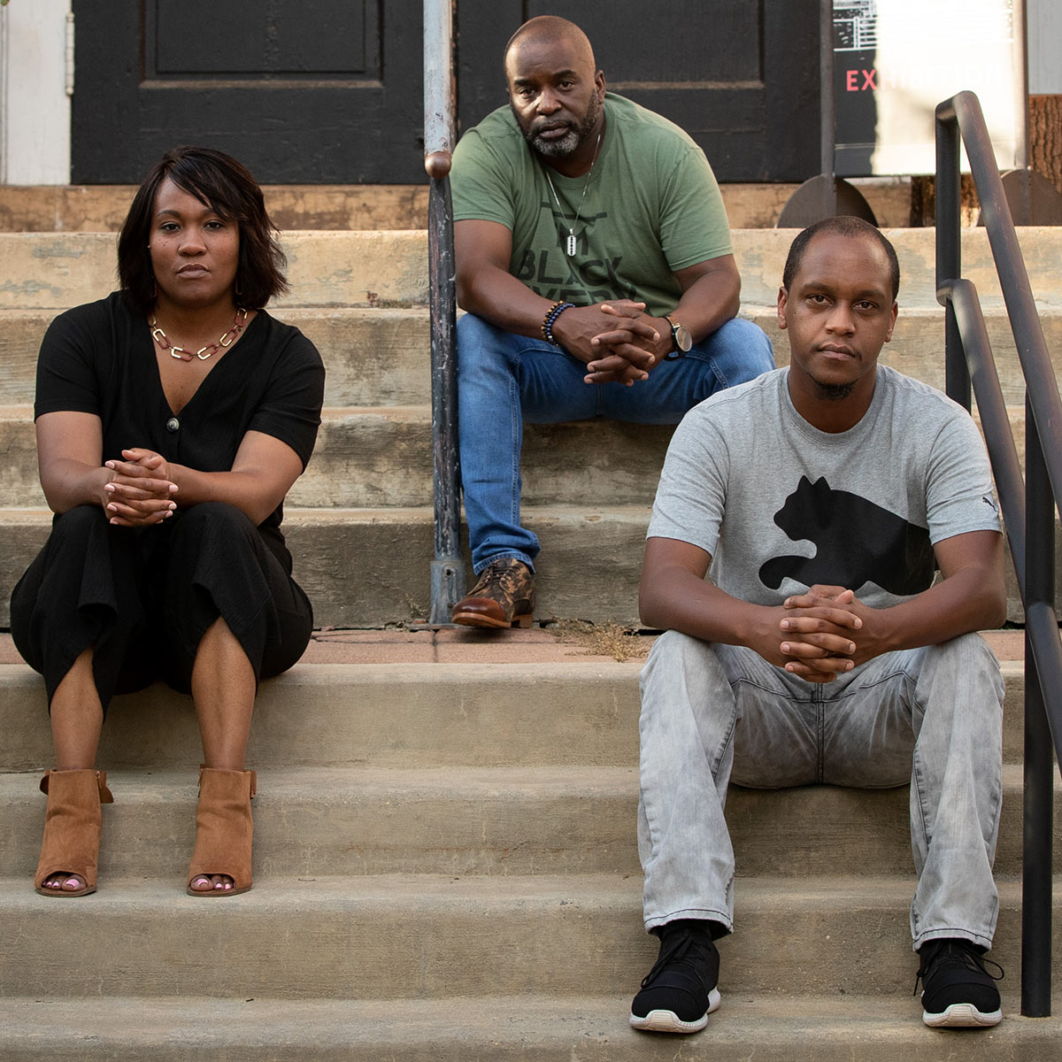 Three black team members of In My Humble Opinion Radio Show sitting on steps in Charlottesville VA